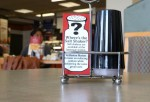 A sign explaining the absence of salt shakers is posted on a table inside a Boston Market restaurant on August 21, 2012 in San Francisco, California. Excessive salt consumption is said to be harmful for the health of the liver.