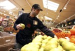 Whole Foods employee Ben Renard stocks shelves with pears at a Whole Foods Market Feb. 22, 2007 in San Francisco, California.
